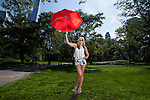 Young Blonde Athletic woman holding a Red Umbrella in Central Park