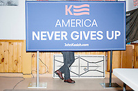 A man sets up a campaign sign backstage to be used as a backdrop for TV interviews before Ohio governor and Republican presidential candidate John Kasich speaks at a town hall campaign event at Raymond VFW Post 4479 in Raymond, New Hampshire, on Wed., Feb. 3, 2016.
