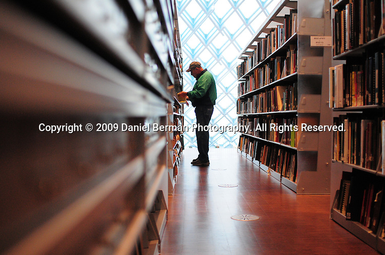 A man browses literature in the Seattle Room of the downtown Seattle Central Library. The 11-story building opened in 2004, and was designed by Rem Koolhaas. Photo by Daniel Berman/www.bermanphotos.com