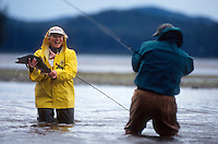 A fishing guide takes a picture of woman holding a pink salmon while fly fishing in Hawk Inlet in Southeast Alaska. M