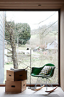 "A full height glass window opening up view over the river is a perfect place to read sitting on an Eames rocker. Beside it stands a 'Tab F1"" light by Barber Ogerby for Flos, wooden boxes by Le Corbusier from Cassina's 'I Maestri' collection."