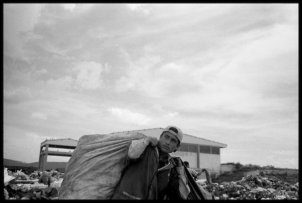 Plastic collector carries his load toward the trucks to be sold.
