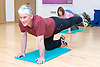 Older man doing floor exercising in an aerobics class at his sports leisure centre,