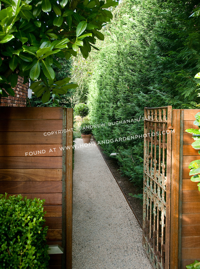 A rusted metal gate offers entry to the stone path leading to the back yard. Design by Scot Eckley, Inc.