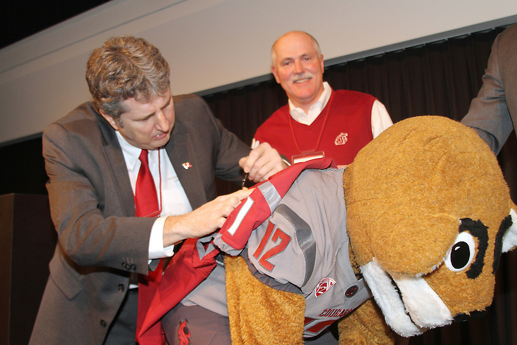"Mike Leach, Washington State head football coach, signs a jersey on the back of WSU mascot, Butch T. Cougar, during the Cougs ""Night with Cougar Football"" at the Tiger Woods Center at Nike headquarters in Beaverton, Oregon, on March 4, 2012."