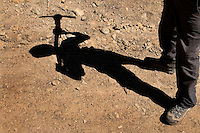 Photo story of Philmont Scout Ranch in Cimarron, New Mexico, taken during a Boy Scout Troop backpack trip in the summer of 2013. Photo is part of a comprehensive picture package which shows in-depth photography of a BSA Ventures crew on a trek.  In this photo a BSA Venture Crew member cast his  shadow across the stone covered ground, as he and his team worked to clear a new trail during the crews conservation project in the backcountry at Philmont Scout Ranch.   <br /> <br /> The  Photo by travel photograph: PatrickschneiderPhoto.com