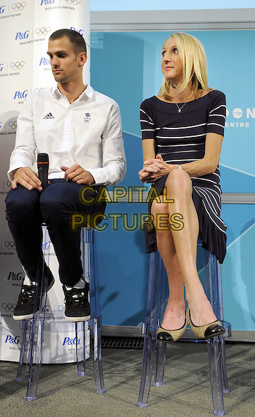 Robbie Grabarz and Paula Radcliffe.Press conference and Photocall to launch P&G's Legacy Commitment to Youth Development through Sport campaign, which will support parents whose children want to take up sport. London Media Centre, London, England..August 9th 2012.full length blue white striped stripes dress white shirt trousers sitting .CAP/BK/PP.©Bob Kent/PP/Capital Pictures.