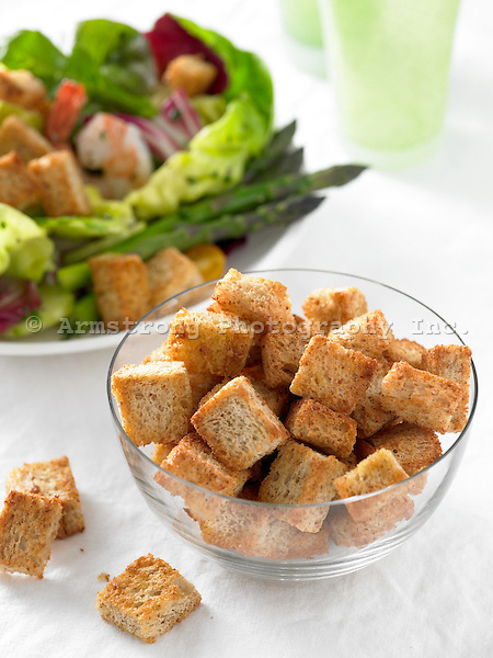 Bowl of croutons with salad in background
