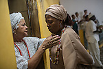 RIO DE JANEIRO, BRAZIL - JANUARY 24: A woman overcome by an orixa is led into a private room by Ekdy Fran&ccedil;a to release the spirit, during a candomble ceremony, in Rio de Janeiro, Brazil, on Saturday, Jan. 23, 2015. Brazil's Afro-Brazilian religions which in recent years have come under increasing threats and prejudice, particularly from the growing number of evangelical churches. Candombl&eacute; originated in Salvador, Bahia at the beginning of the 19th century when enslaved Africans brought their beliefs with them. Umbanda and candombl&eacute; are Afro-Brazilian religions practiced in mostly Brazil. <br /> (Lianne Milton for the Washington Post)