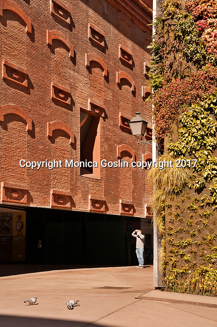 Green wall of plants and a small plaza in front of the Caixa Forum, an arts center in former power station, hosting exhibitions and performances in Madrid, Spain