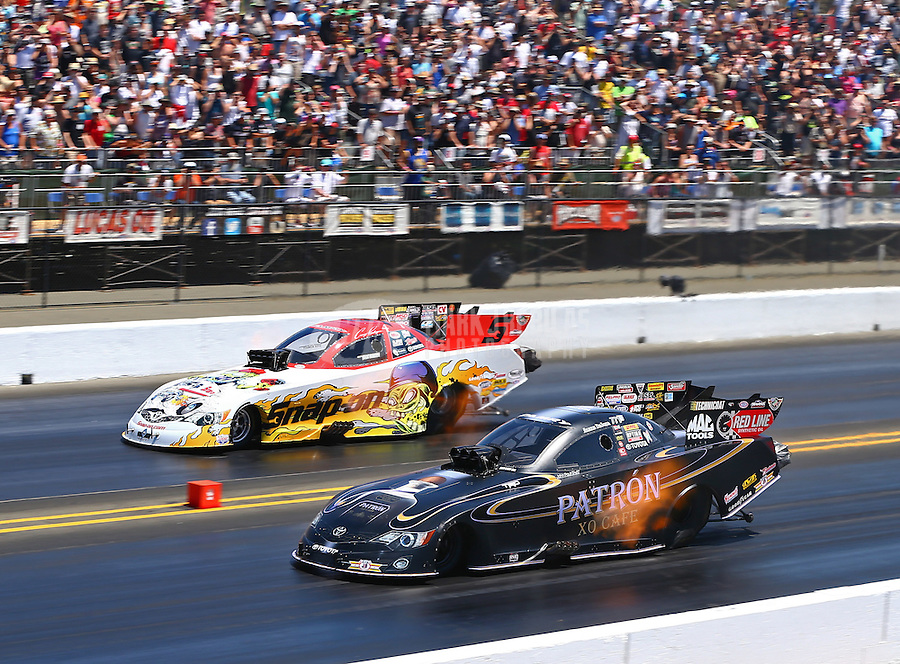 Jul. 27, 2014; Sonoma, CA, USA; NHRA funny car driver Alexis DeJoria (near) races alongside Cruz Pedregon during the Sonoma Nationals at Sonoma Raceway. Mandatory Credit: Mark J. Rebilas-