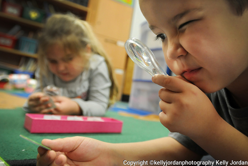 "Kelly.Jordan@jacksonville.com--111011--Dylen Ford, 5, uses a magnifying glass to sort photographs of the seasons and match them with the time of year they fall during science time in his kindergarten class at John A. Crookshank Elementary School in St. Augustine Thursday November 10, 2011. Teachers like his kindergarten teacher Shea Grammer are spending more of their own money to pay for classroom supplies. Grammer was one of the lucky ones because she is among 54 Jacksonville area teachers who has received donations totaling more than $30,000 to fund 68 classroom projects through Donors Choose, a non-profit organization that connects donors with public school teachers who need classroom materials. Grammer got money for a hands-on science learning project entitled ""Exploring Science"" which fits with her goal to ""make science fun.""(The Florida Times-Union, Kelly Jordan)"