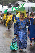 London, UK. 25 August 2014. Some participants braced the parade in style - with the help of large umbrellas. Visitors and participants of the Notting Hill Carnival 2014 Bank Holiday Monday parade got soaked to their skin, but the weather couldn't dampen the revellers spirit - although many spectators stayed away.