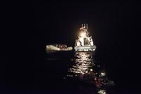 Die Sea Watch-2 Crew war am Freitag den 21. Oktober 2016 in den fruehen Morgenstunden waehrend ihrer 13. SAR-Mission vor der libyschen Kueste zu einer Position ausserhalb der 12 Meilenzone gerufen worden. Es war ein Fluechtlingsschlauchboot gesichtet worden. Als die Sea Watch-2 dort eintraf sah sie ca. 150 Menschen zusammengepfercht in einem ueberfuellten Schlauchboot sitzen. Eine Versorgung der Menschen auf dem Fluechtlingsschlauchboot mit Rettungswesten durch die Rettungs Boote der Sea Watch-2 wurde von der libyschen Kuestenwache unterbunden. Ein Soldat der Kuestenwache enterte das Schlauchboot vom Bug und machte sich dann an dem Aussenbordmotor zu schaffen. Auf dem Weg dahin schlug und trat er die Gefluechteten ein. Nach einigen Minuten entfernte sich das Boot der Kuestenwache. Dann verlor der Bug des Schlauchbootes seine Luft und es brach Panik bei den Gefluechteten aus. Sie sprangen in das Wasser und versuchten zum Schiff Sea Watch-2 zu gelangen. Die Crew warf ihnen Schwimmwesten und Rettungsringe zu, die Besatzungen der Rettungsboote der Sea Watch-2 zogen Menschen aus dem Meer, dennoch sind bis zu 30 Menschen ertrunken. Vier Ertrunkene konnten von der Sea Watch geborgen werden.<br /> Im Bild: Das Schiff der Libyschen Kuestenwache neben dem Fluechtlingsschlauchboot.<br /> Vorne: Ein abgedraengtes Rettungsboot der Sea Watch-2.<br /> 21.10.2016, Mediterranean Sea<br /> Copyright: Christian-Ditsch.de<br /> [Inhaltsveraendernde Manipulation des Fotos nur nach ausdruecklicher Genehmigung des Fotografen. Vereinbarungen ueber Abtretung von Persoenlichkeitsrechten/Model Release der abgebildeten Person/Personen liegen nicht vor. NO MODEL RELEASE! Nur fuer Redaktionelle Zwecke. Don't publish without copyright Christian-Ditsch.de, Veroeffentlichung nur mit Fotografennennung, sowie gegen Honorar, MwSt. und Beleg. Konto: I N G - D i B a, IBAN DE58500105175400192269, BIC INGDDEFFXXX, Kontakt: post@christian-ditsch.de<br /> Bei der Bearbeitung der Dateiinformationen darf die 