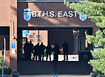 "Members of area tactical units silhouetted in the breezeway outside the administrative offices as seen from the student parking lot side of Belleville East High School Wednesday morning May 3, 2018 after a ""credible threat"" forced the school district to cancel classes and shut down the school at both East and Belleville West High School before students reported for class.  Photo by Tim Vizer"