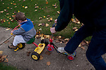 My husband and older son, then three, play outside together, my husband on our son's scooter.