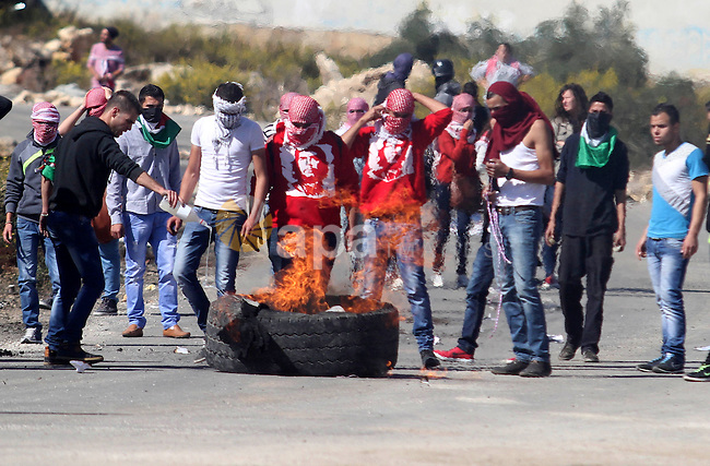 Palestinian protesters burn tires during clashes with Israeli security forces at a protest to show solidarity with al-Aqsa mosque, outside Israel's Ofer military prison near the West Bank city of Ramallah October 21, 2014. A Palestinian official on Monday called for holding an emergency Arab and Islamic summit to discuss Israeli plans to divide the Al-Aqsa Mosque compound between Jews and Muslims. In recent months, groups of Jewish settlers accompanied by Israeli security forces have repeatedly forced their way into East Jerusalem's flashpoint Al-Aqsa Mosque. Photo by Shadi Hatem