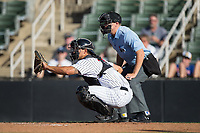 Kannapolis Intimidators catcher Seby Zavala (21) sets a target as home plate umpire Aaron Schorch looks on during the game against the Lakewood BlueClaws at Kannapolis Intimidators Stadium on April 9, 2017 in Kannapolis, North Carolina.  The BlueClaws defeated the Intimidators 7-1.  (Brian Westerholt/Four Seam Images)