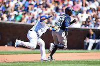 Chicago Cubs second baseman Javier Baez (9) tags out Carlos Gomez (27) in a rundown during a game against the Milwaukee Brewers on August 14, 2014 at Wrigley Field in Chicago, Illinois.  Milwaukee defeated Chicago 6-2.  (Mike Janes/Four Seam Images)