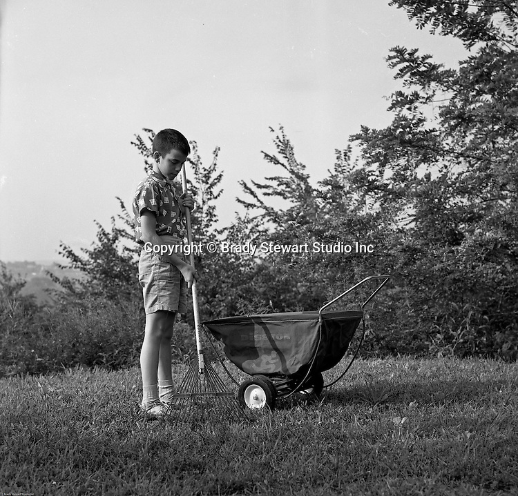 Bethel Park PA:  Brady Stewart III raking grass in the back yard and using a Disson Leaf Wheelbarrow.  Another modeling assignment for a member of the Stewart family.