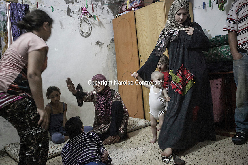 June 09, 2015 - Beirut, Lebanon: Widaad (right) holds her son Aïssa as her daughter Houda (right bottom) stands behind at their room house in Shatila refugee camp. They are Syrian refugees from the city of Al Qusayr from where they fled four years ago when the fighting sparked out between opposition armed groups against loyalists to President Bashar Al-Assad. Left to the frame is pictured also Ammal Akkar and two of her daughters, all them Palestinian refugees. (Photo/Narciso Contreras)