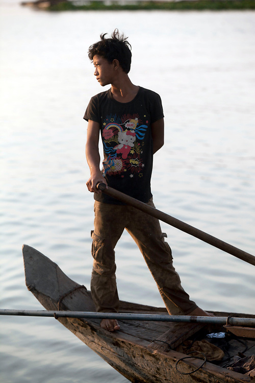 Portrait of a young fisherman at work on the Mekong River early in the morning outside of Phnom Penh, Cambodia. <br /> <br /> Photos &copy; Dennis Drenner 2013.