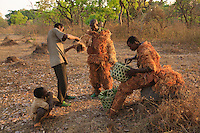 After a very poor harvest, the honey gatherers take off the heavy suits that protected them from stings.
