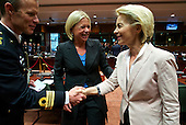 German defence minster Ursula von der Leyen meets an unidentified person at the EU Council. Dutch defence minister Jeanine Hennis-Plasschaert is in the middle.