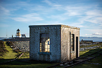 An abandoned building on Ailsa Craig, an unihabited volcanic island that is the source of the granite used to make most of the world's curling stones, including those used every four years in the Winter Olympics. The island's lighthouse is in the background.