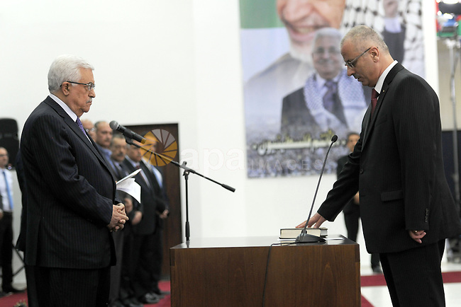Palestinian Prime Minister Rami Hamdallah swears in during the oath ceremony in the West Bank city of Ramallah, 06 June 2013. Hamdallah and 24 ministers on 06 June took the oath before Palestinian President Mahmoud Abbas after a decision of reshuffling the government. Abbas chose the 54-year-old academic for the post after Salam Fayyad resigned in April and asked him to form a government. Photo by Thaer Ganaim