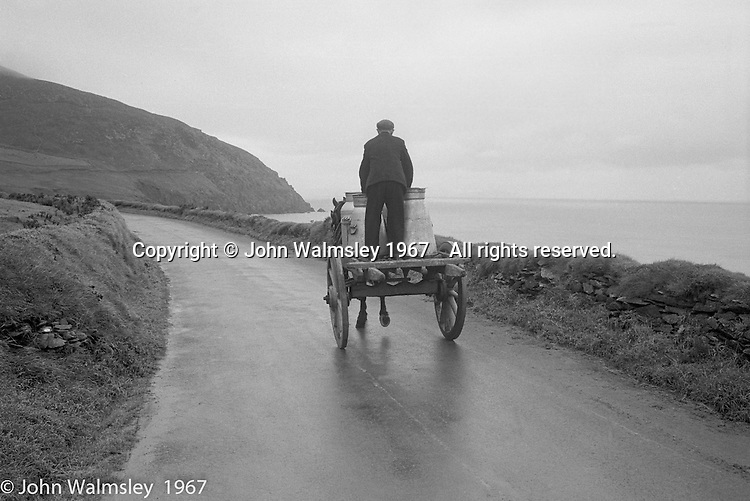 """Donkey cart carrying milk churns, Dunquin (in Gaelic, Dún Chaoin, meaning """"Caon's stronghold""""), on the tip of the Dingle Peninsula, County Kerry, Ireland.  1971."""