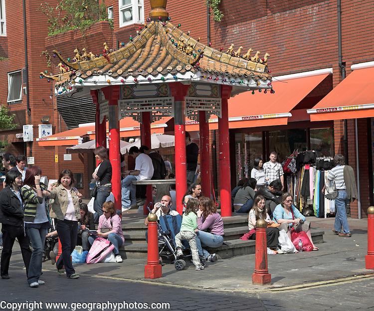 People sit around pagoda, Chinatown, Soho, London, England