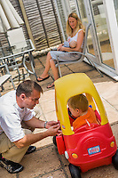 A woman sits in a patio chair outside her conservatory and breastfeeds her baby wilst her husband talks to her older child who is riding in a plastic ride-in car.<br /> <br /> 09/07/2011<br /> Hampshire, England, UK