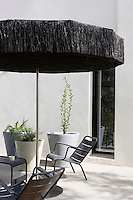 A pair of black-painted garden chairs is shaded by a black fringed parasol on the terrace
