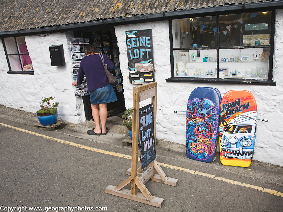 Woman browsing postcards at the village of Coverack on the Lizard peninsula, Cornwall, England