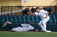 Lakeland Flying Tigers first baseman James Robbins (7) takes a throw as outfielder Jake Cave (18) dives back to first during a game against the Tampa Yankees on April 5, 2014 at Joker Marchant Stadium in Lakeland, Florida.  Lakeland defeated Tampa 3-0.  (Mike Janes/Four Seam Images)