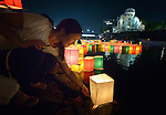 A woman sets a floating candle lantern on the river on August 6, 2015, in Hiroshima, Japan. The lanterns, thousands of which were launched on the 70th anniversary of the atomic bombing of the city, carried handmade messages and drawings, conveying each person's prayers for peace and comfort for the victims of the violence. In the background are the ruins of a building damaged by the bomb and now converted into a peace memorial.
