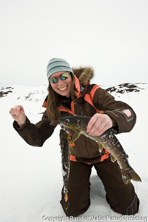Jente har fått to ørreter på isfiske ---- Girl catching trout