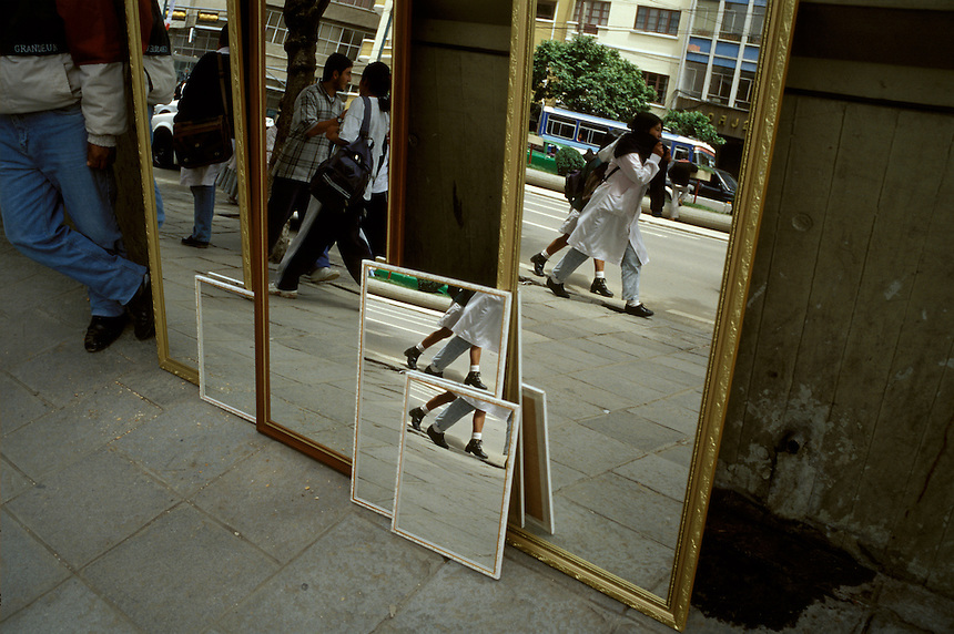 A mirror vendor in La Paz, Bolivia, lets the world reflect in his wares on a busy city street.