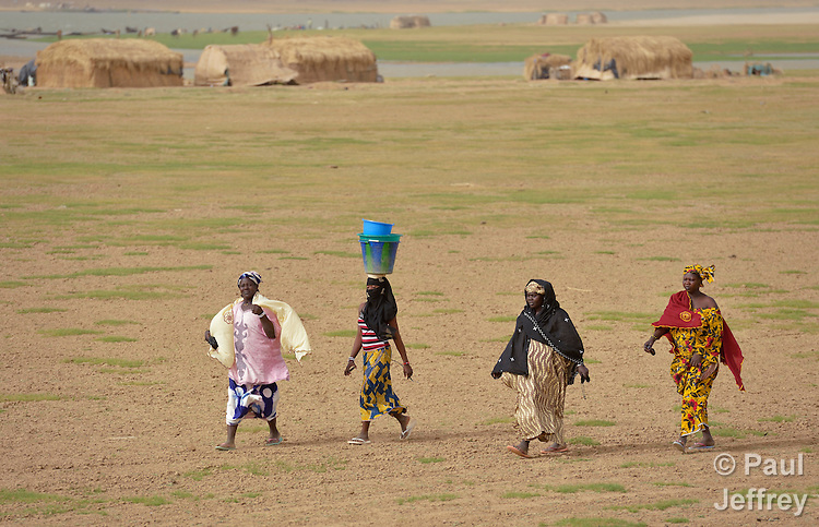 Women walking across the arid landscape near Toya, a village in northern Mali near Timbuktu. The region was seized by Islamist fighters in 2012 and then liberated by French and Malian soldiers in early 2013.