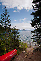 A red canoe at the Merritt Lane campsite on Tobin Harbor at Isle Royale National Park in Michigan USA.