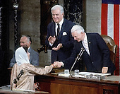 Washington, D.C. - (FILE) -- Prime Minister Benazir Bhutto of Pakistan, left, shakes hands with United States Senator Robert Byrd (Democrat of West Virginia), the President pro tempore of the United States Senate, right, as Speaker of the House Tom Foley (Democrat of Washington) applauds, center, following her address to a joint session of the United States Congress in Washington, D.C. on Wednesday, June 7, 1989.  Bhutto was assassinated in Rawalpindi, Pakistan on Thursday, December 27, 2007 after appearing at a campaign rally there..Credit: Howard L. Sachs / CNP
