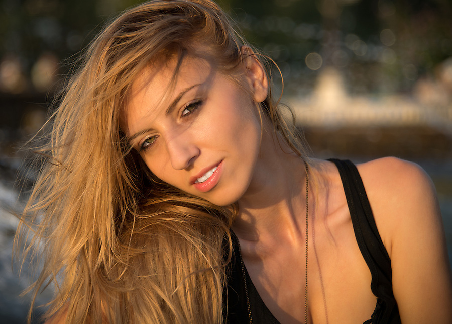 Attractive young blonde woman looking at the camera smiling in the golden glow of evening sunlight