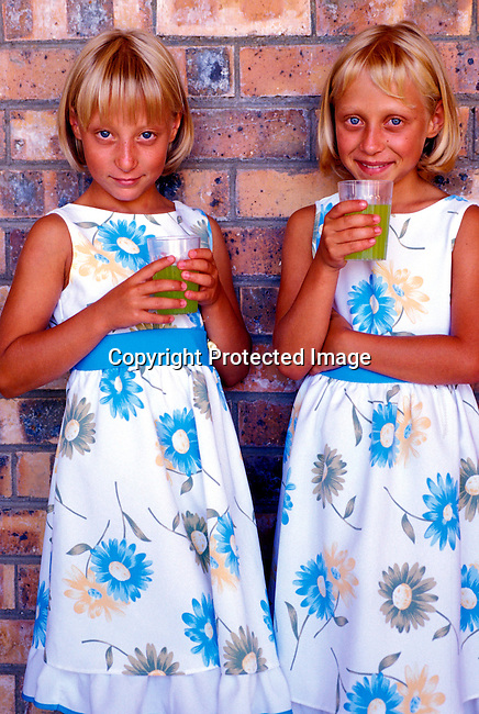 DIPOAFR00037.Culture Afrikaners Anneze and Carla Bornman, age 8, twin girls drinking lemonade after a Sunday morning service at the APK church in Orania, South Africa. Orania is an Afrikaner community only for white people. Nor colored people are allowed in this community of about 600 people. .Photo: Per-Anders Pettersson/ iAfrika Photos