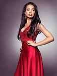Beautiful young black woman wearing red dress isolated on gray background