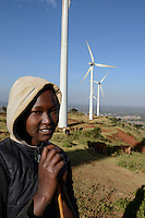 KENYA, Nairobi, Ngong Hills, 25,5 MW Wind Power Station with Vestas and Gamesa wind turbines, owned and operated by KENGEN Kenya Electricity Generating Company, shepherd with cows / KENIA, Ngong Hills Windpark, Betreiber KenGen Kenya Electricity Generating Company mit Vestas und Gamesa Windkraftanlagen, junge Hirtin mit Kuehen