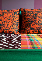 The bed is covered in checked and polka dot bedding with bright orange cushions printed with a cartoon motif