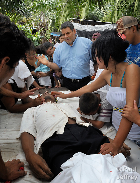 The Rev. Juan Guerrero, a United Methodist missionary and superintendent of the United Methodist Mission in Honduras, prays over the body of Carlos Martinez, a 23-year old farmworker who was shot to death on October 2, 2011, on the La Lempira Cooperative outside Tocoa, Honduras. Martinez and other members of the cooperative are among thousands of Honduran activists who have seized plantations they claim were stolen from them by wealthy Honduras businessmen. Honduran security forces have militarized the area, and killings of peasant leaders have become common. Many of the cooperatives were started with assistance from Catholic priests and lay pastors in the region. A sister of Martinez claimed he was killed by a security guard from a nearby plantation belonging to Miguel Facusse, the wealthiest of Honduran landowners.