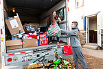 WOLCOTT, CT. 23 December 2018-122318 - Stephen Tedd, 13, of Wolcott, right, helps out by giving his mom Brandi Nichols of Wolcott a bag of gifts at the Grange in Wolcott on Sunday. The gifts will be distributed on Christmas Day with help from the Waterbury Fire and Police departments to families less fortunate for the holidays. Bill Shettle Republican-American