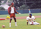 Washington Redskins receivers head coach Charlie Taylor speaks with wider receiver Art Monk (81) as he does looks warm-up exercises during Washington Redskins training camp at Dickinson College in Carlisle, Pennsylvania on July 26, 1993.<br /> Credit: Ron Sachs / CNP